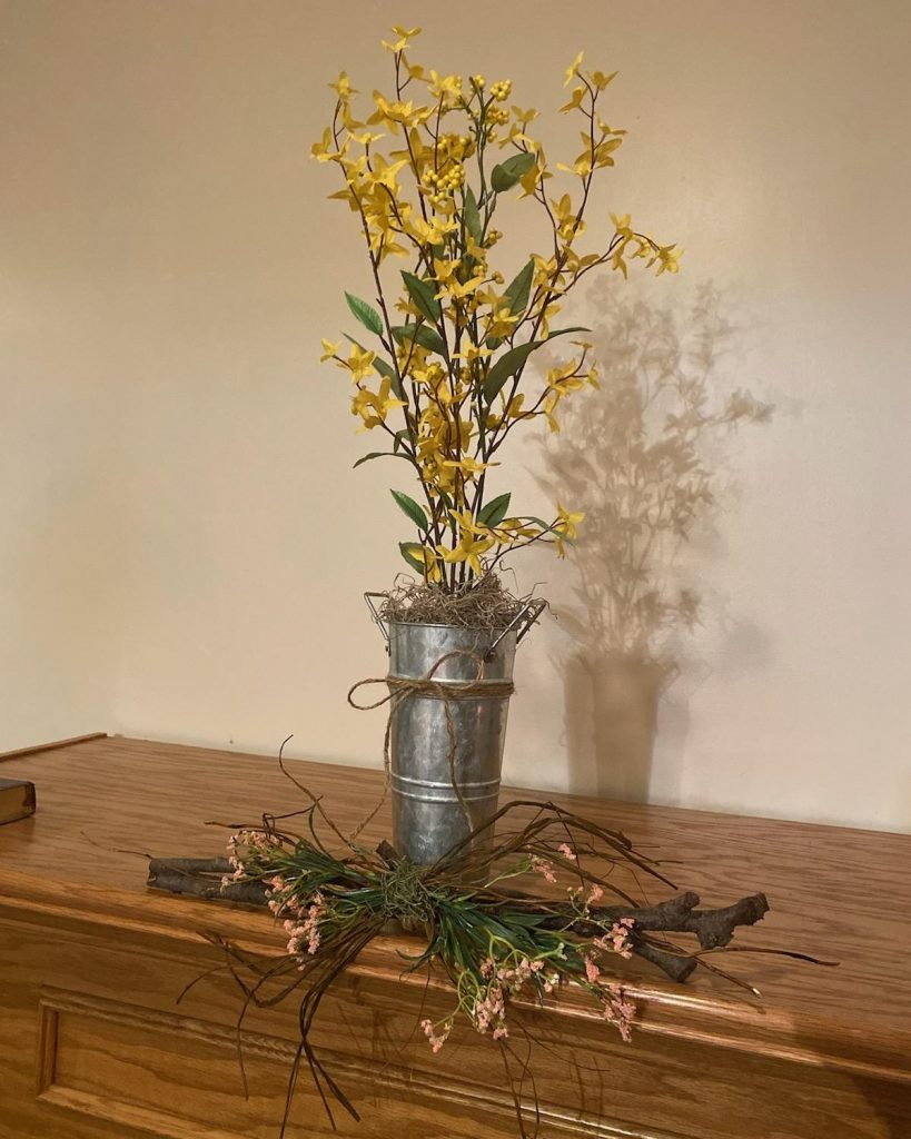 metal vase with faux yellow flowers